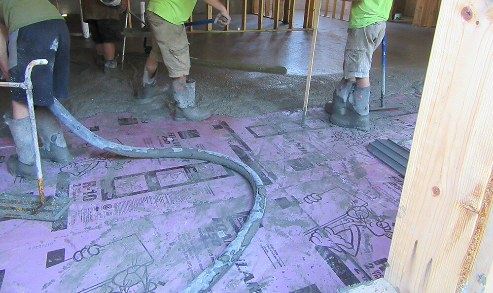 Continuous insulation being installed under the floor of a residential building project