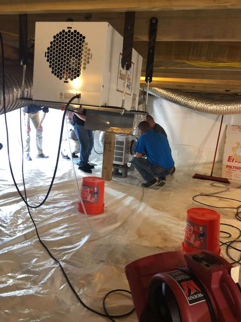 An insulation crew working on a crawl space